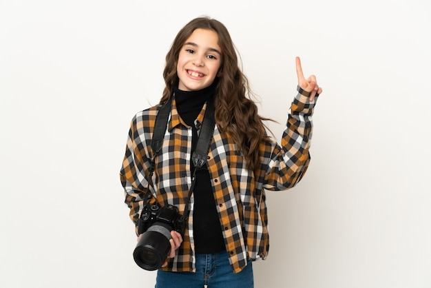 작은 사진 작가 소녀는 최고의 기호에 손가락을 보여주는 벽에 격리