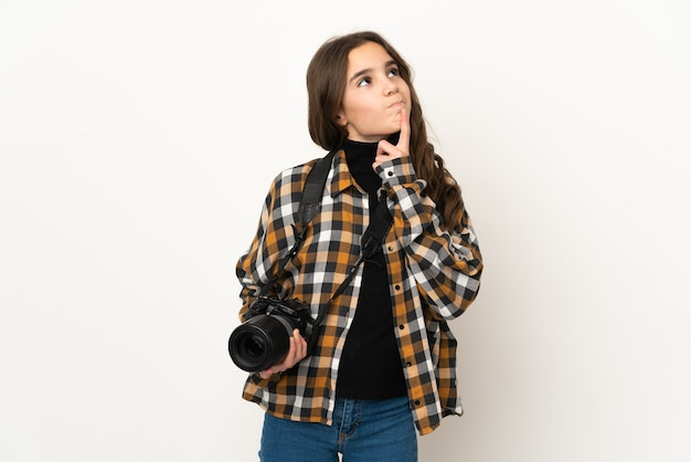 Little photographer girl isolated on wall having doubts while looking up