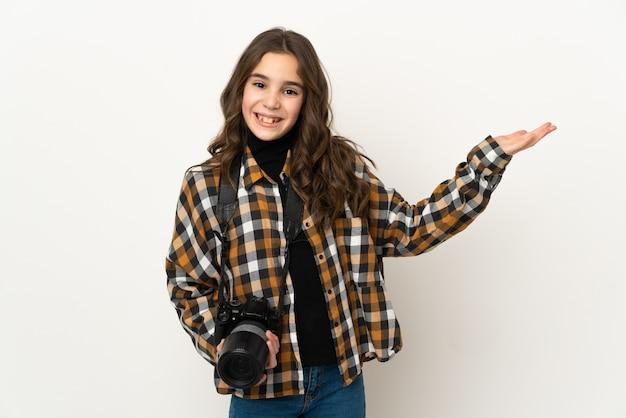 小さな写真家の女性が壁に孤立し、手を横に伸ばして招待します