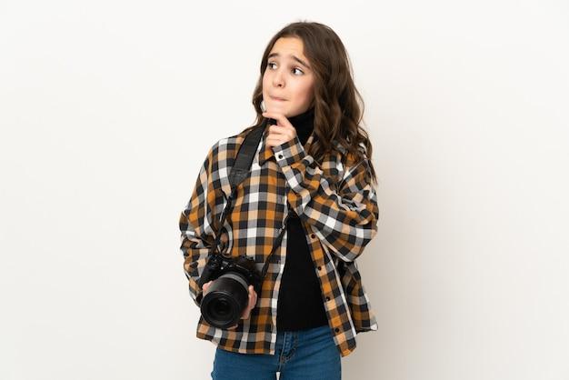 疑いと思考を持って壁に孤立した小さな写真家の女性