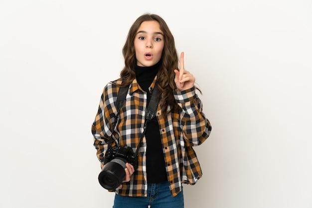 指を持ち上げながら解決策を実現しようと壁に孤立した小さな写真家の女性