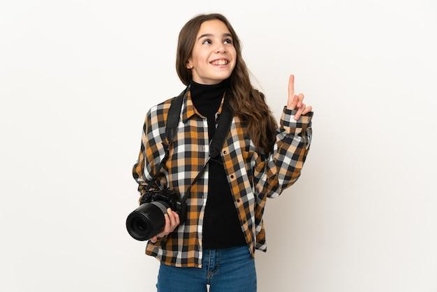 指を上に向けるアイデアを考えて壁に孤立した小さな写真家の女性