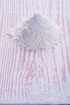 古い白い机の上に小麦粉の小さな山