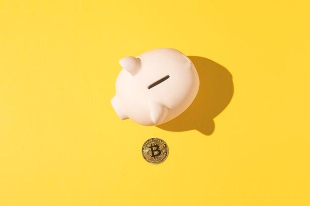 黄色の背景に小さなピンクのセラミック貯金箱とビットコイン。暗号通貨の概念、お金と節約の節約。