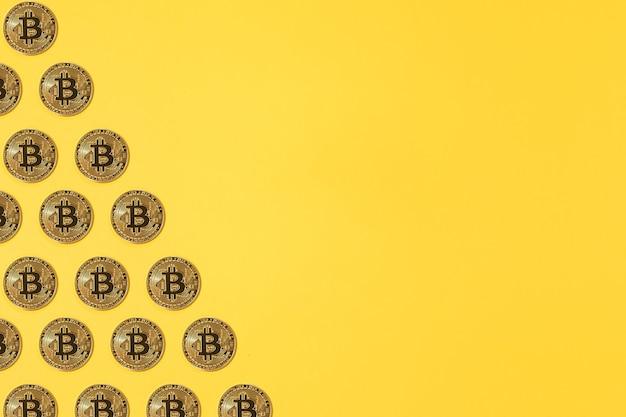 黄色の背景の左側に小さなピンクのセラミック貯金箱のパターン。暗号通貨の概念、お金と節約の節約。