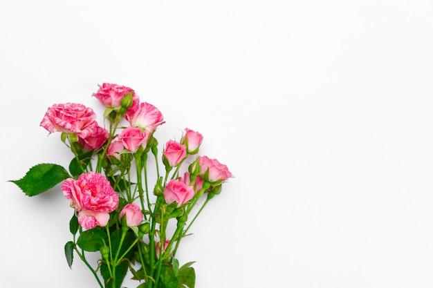 白いテーブルに小さなピンクのバラ。穏やかなロマンチックな背景。花の背景