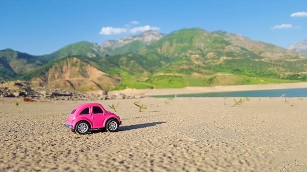 Маленький розовый игрушечный автомобиль на фоне природы. летние каникулы, концепция путешествия.