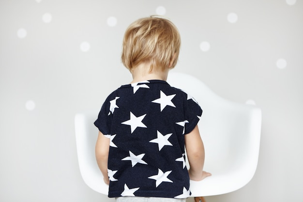 Little playful caucasian boy with blonde hair dressed in t-shirt with stars, playing with his toys in nursery. rear view of adorable sweet toddler in front of white chair at home.