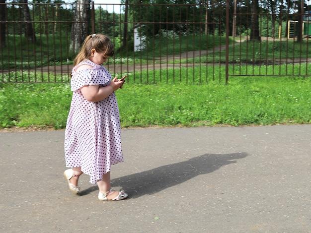 Маленькая пухленькая девочка идет по пустынной парковой дорожке, глядя на смартфон