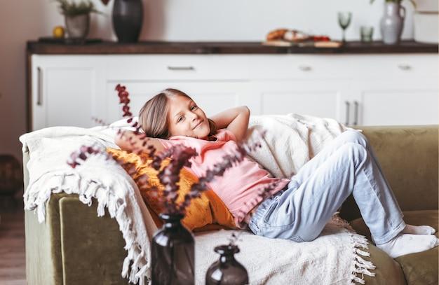 Маленькая позитивная девочка отдыхает на диване в комнате