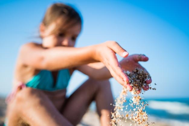 긍정적인 어린 소녀는 해변에 앉아 휴가 기간 동안 화창한 여름날 바다 파도를 즐깁니다. 아이들과 함께하는 가족 휴가의 개념