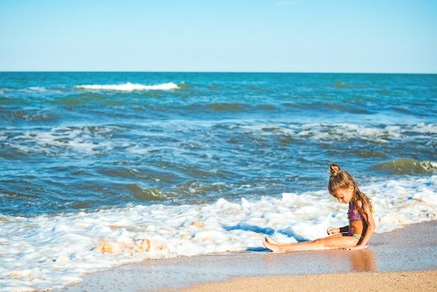 小さなポジティブな女の子が海岸に座って、休暇中の晴れた夏の日に海の波を楽しんでいます。子供との家族の休日の概念