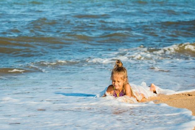 小さなポジティブな女の子が海岸に座って海の波を楽しんでいます