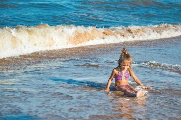 작은 긍정적인 소녀는 해변에 앉아