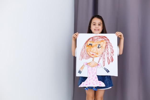 그녀의 초상화 사진을 들고 어린 취학 전 소녀