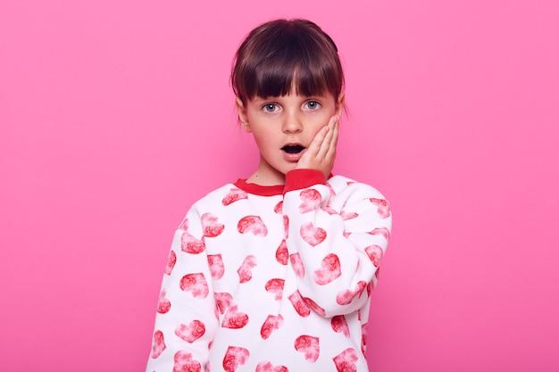 Маленькая дошкольница смотрит в камеру с открытым ртом, прикрывает щеку ладонью, одетая в повседневную одежду, изолированную на розовой стене.