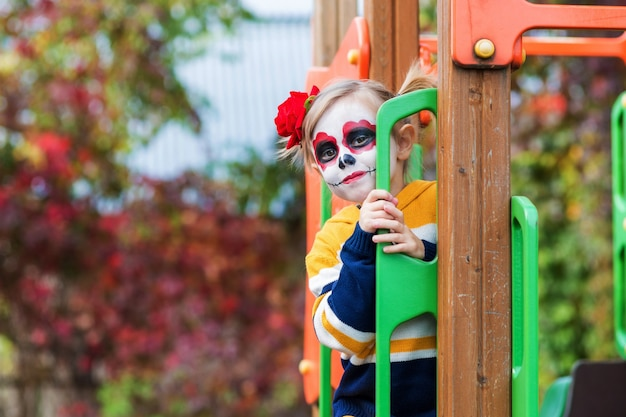 A little preschool girl with painted face, climbed the slide on the playground, celebrates halloween or mexican day of the dead.