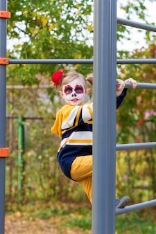 A little preschool girl with painted face, climbed the swedish wall in the playground, celebrates halloween or mexican day of the dead.