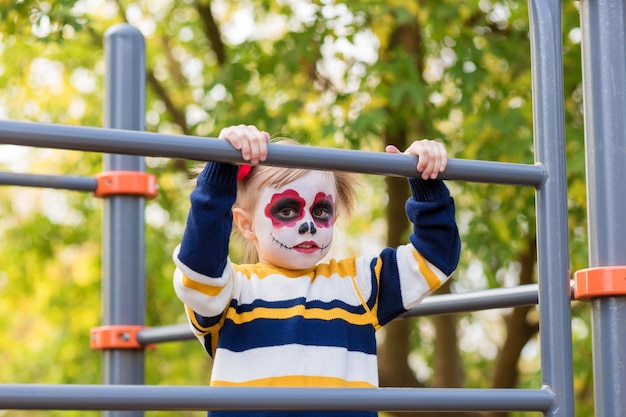 A little preschool girl with painted face, looking on the playground, celebrates halloween or mexican day of the dead..