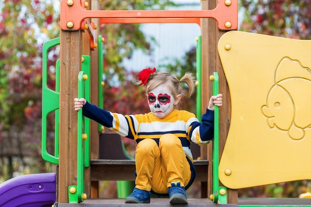 A little preschool girl with painted face, rides a slide on the playground, celebrates halloween or mexican day of the dead.