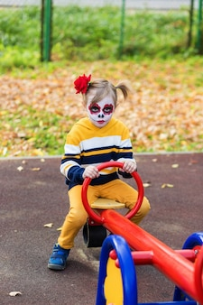 A little preschool girl with painted face, rides on a swing in the playground, celebrates halloween or mexican day of the dead.