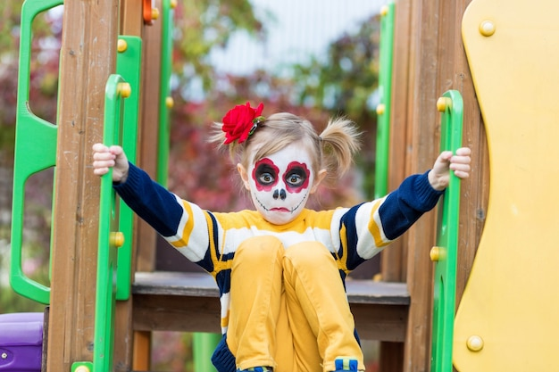 A little preschool girl with painted face, shows funny faces on the playground, celebrates halloween or mexican day of the dead.