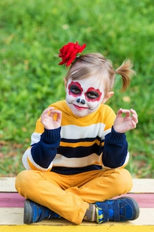 A little preschool girl with painted face, sitting on a bench in lotus position on the playground, celebrates halloween or mexican day of the dead.