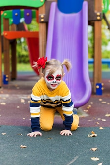 A little preschool girl with painted face, smiling on the playground, celebrates halloween or mexican day of the dead..