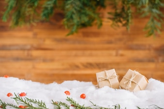 Little presents in snow with conifer branches