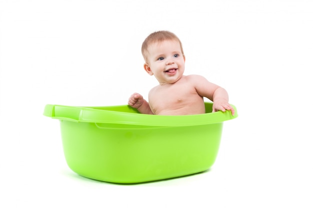 Little pretty baby boy take bath in green tub