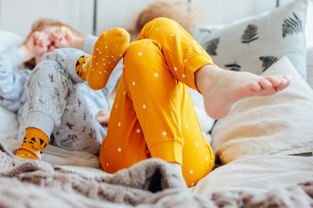Little pretty brother and sister in pajamas lying in bed, cozy m
