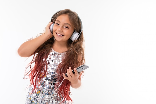Little pretty caucasian girl listen to music with big earphones, picture isolated on white wall