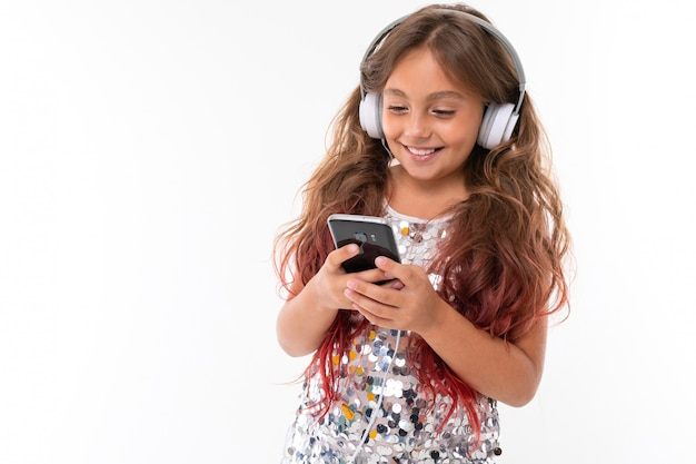 Little pretty caucasian girl listen to music with big earphones and serfing internet with phone, picture isolated on white wall