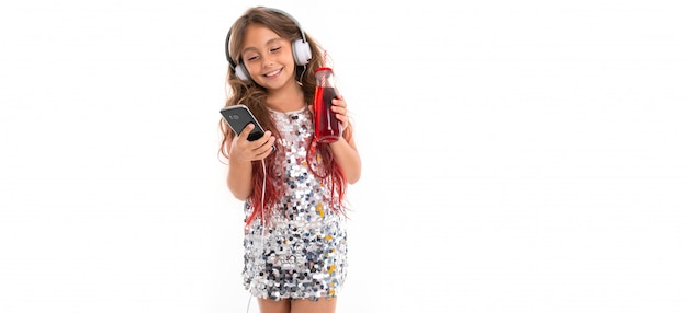 Little pretty caucasian girl listen to music with big earphones and smiles, pa isolated on white wall