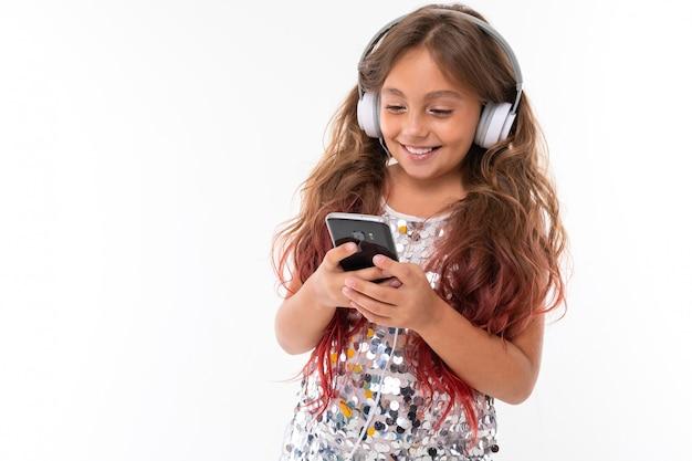 Маленькая милая кавказская девушка слушает музыку с большими наушниками и серфует интернет с телефоном, картинка на белой стене