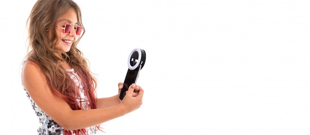 Little pretty caucasian girl do selfie with phone and circle lamp, panorama isolated on white wall