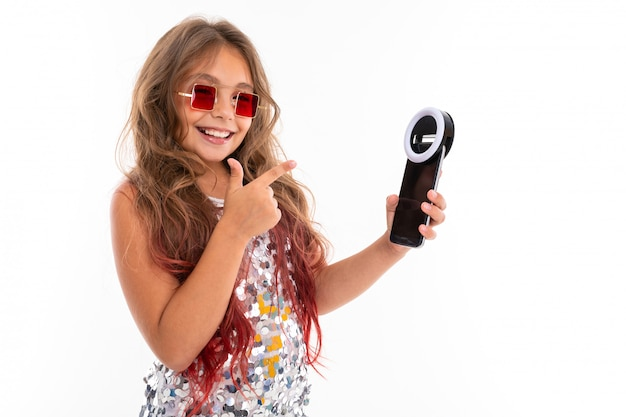 Little pretty caucasian girl do selfie with phone and circle lamp, picture isolated on white wall