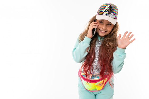 Little pretty caucasian girl in a tracksuit call the phone and smiles, picture isolated on white wall