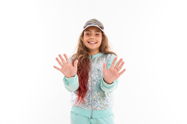 Little pretty caucasian girl in a tracksuit wave hands, picture isolated on white wall
