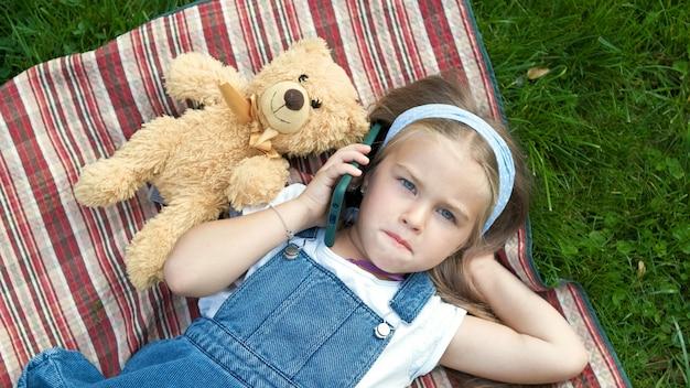 彼女のテディベアと夏に緑の芝生の毛布の上に横たわっている小さなかわいい子供の女の子