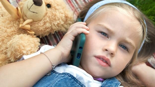 彼女のテディベアが携帯電話で話している緑の芝生の毛布の上に横たわっている小さなかわいい子供の女の子