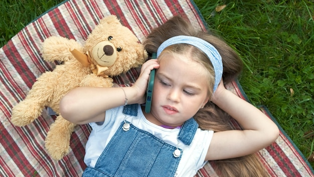 彼女のテディベアのおもちゃが携帯電話で話している夏の緑の芝生の毛布の上に横たわっている小さなかわいい子供の女の子。