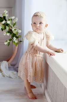 Little pretty girl barefoot is by the window. lovely little girl 1 year old does the first steps