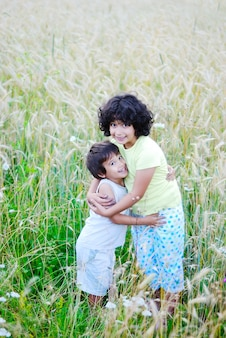 A little pretty girl and boy on green medow