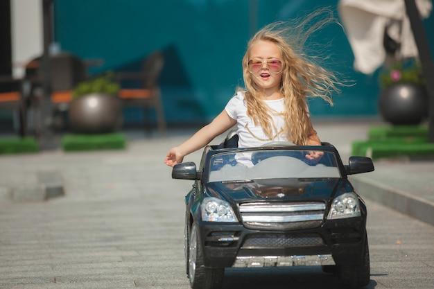 차를 운전하는 예쁜 소녀. 자동차를 운전하는 아이. 어른처럼