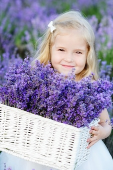 Little pretty girl holding lavender in the basket