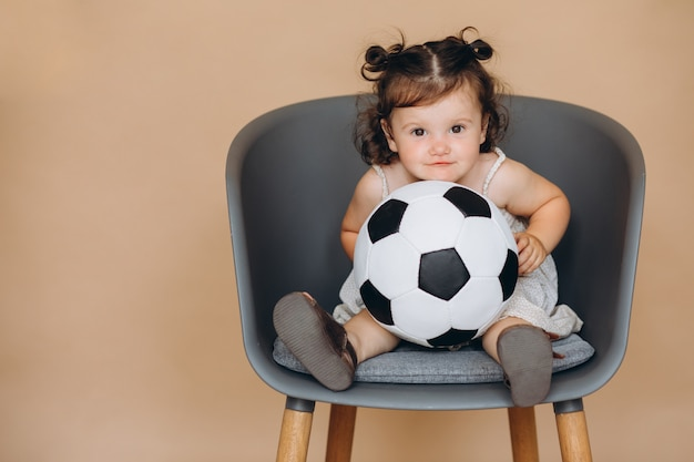 A little pretty girl holds the ball and watches football and cheers for her team