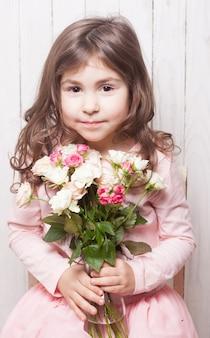 ピンクの小さなかわいい女の子はバラの花束を持っています。花と顔をクローズアップ