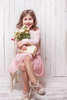 ピンクの小さなかわいい女の子はバラの花束を持っています。椅子に座っているお嬢様