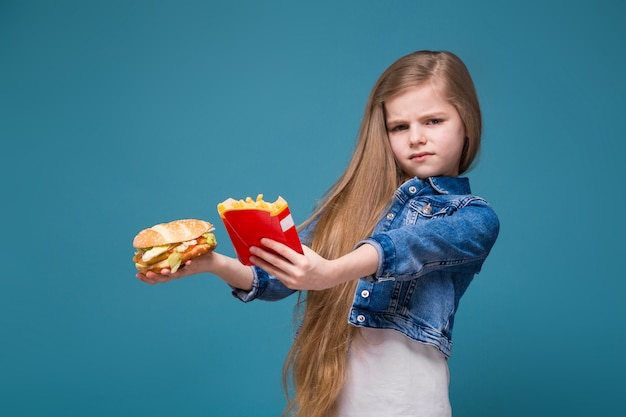 Little pretty girl in jean jacket with long brown hair hold a burger and fried potato